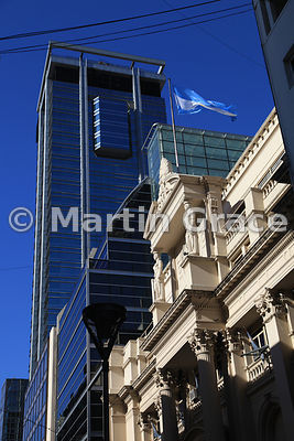 Stone building of the Central Bank of the Argentine Republic, Buenos Aires flying Argentine flag contrasted with modern skyscraper