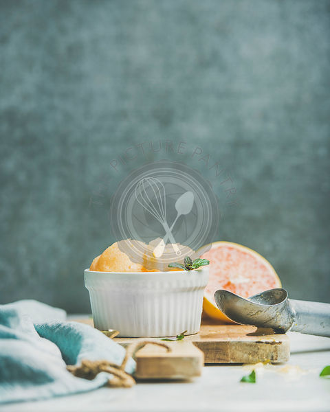 Pink grapefruit homemade sorbet with fresh mint leaves in white bowl on wooden board, grey plywood wall at background
