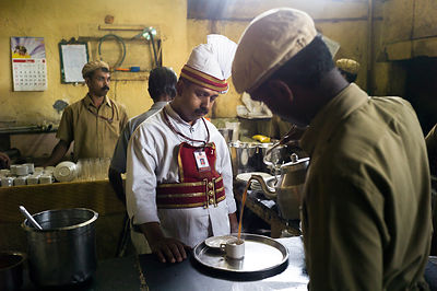 India - Kottayam - A waiter looks exhausted as he waits for a cup of tea to be poured in the kitchen in the Indian Coffee House
