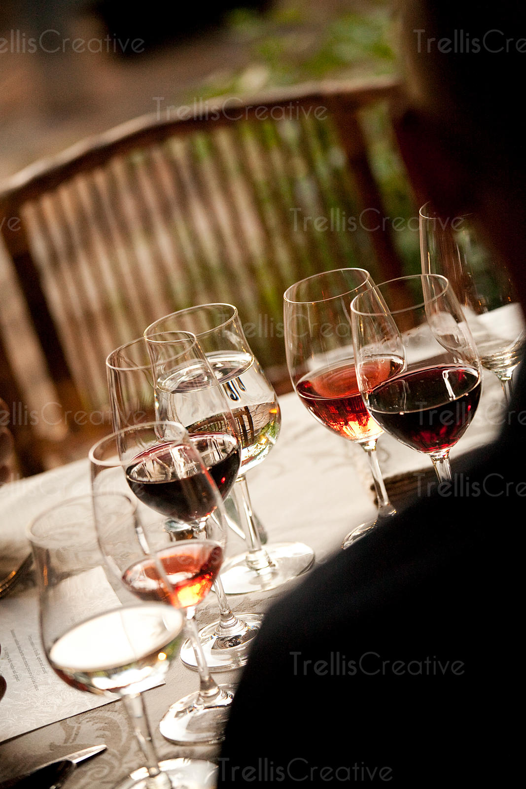 Looking over a guest's shoulder at wine glasses on a table