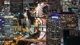 Bird's Eye: Close Up of a Brightly Lit Los Angeles Highway Snaking Through the Lights of Downtown