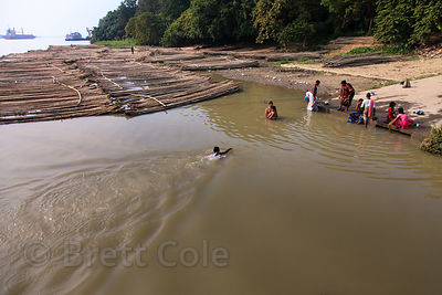 A man swims in the Hooghly River next to a pile of bamboo, near Metiabruz, Kolkata, India.
