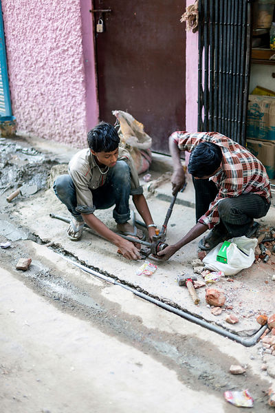 India - Delhi - Two men plumb in and cement illegal water pipes in the Munika area