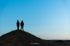 Silhouette of two people standing on hill in the South Gobi Desert, Mongolia.  In the Khongoryn Els sand dunes in Gobi Gurvansaikhan National Park