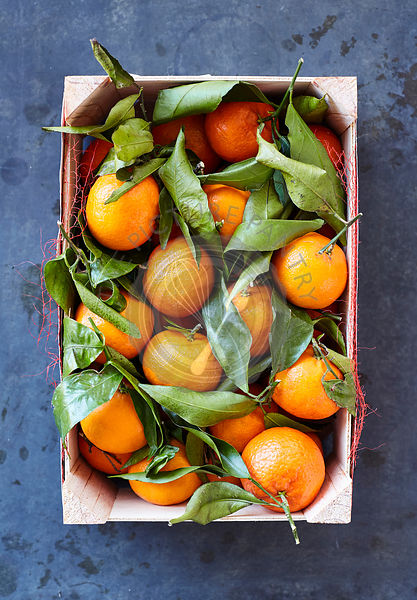 Clementines with leaves in wooden crate