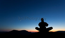 Man Praying on the summit of a mountain.