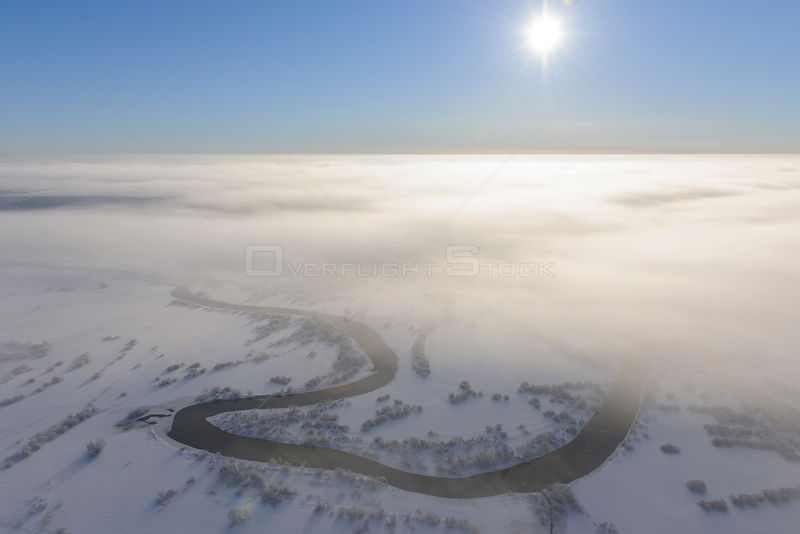 Aerial view over Suur-Emajagi river through the clouds. Estonia, winter  2011.