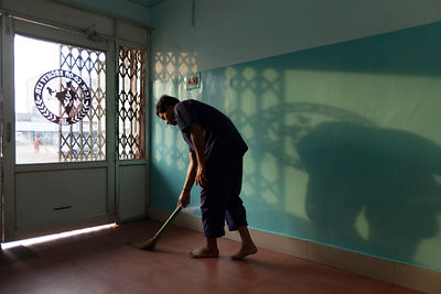 India - Korba - A worker sweeps the floor as early morning light streams through a door throwing a shadow on the wall of the Indian Coffee house logo. Transport Nagar