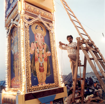 Pilgrims on their bus at the KAn electrician at work on pillar depicting the God Ganesh at the Kumbh Melaumbh Mela