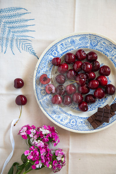 whole cherries and chocolate on blue ceramic plate, with leaf motif table linen and flowers