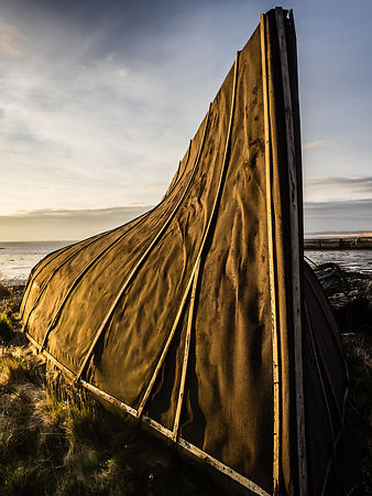 Early morning sun on upturned boat, Lindisfarne, The Holy Isle, Northumberland
