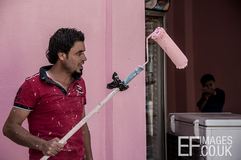 A Moslawi man gets to work painting over the bullet holes left in his shop front by the ISIS conflict in a rather fetching shade of blancmange pink. West Mosul, 5th June 2017