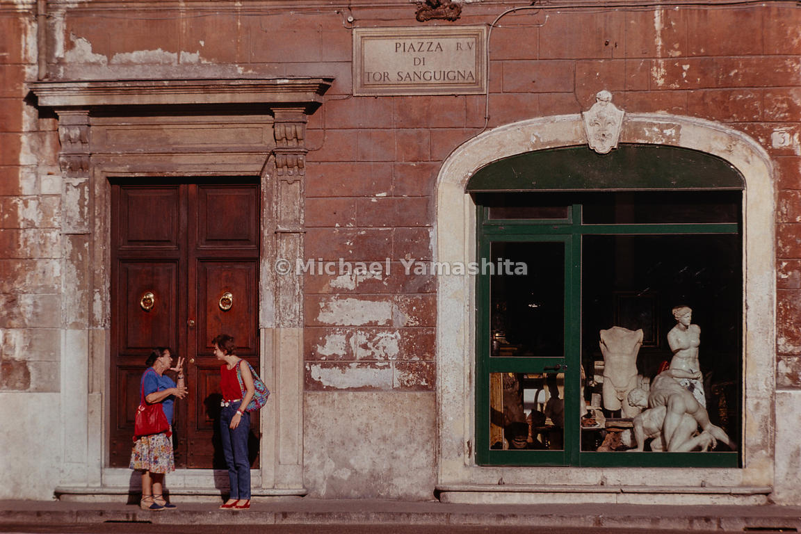 Women converse near a window with sculptures in the Piazza di Tor Sanguigna. Rome, Italy, 1988.