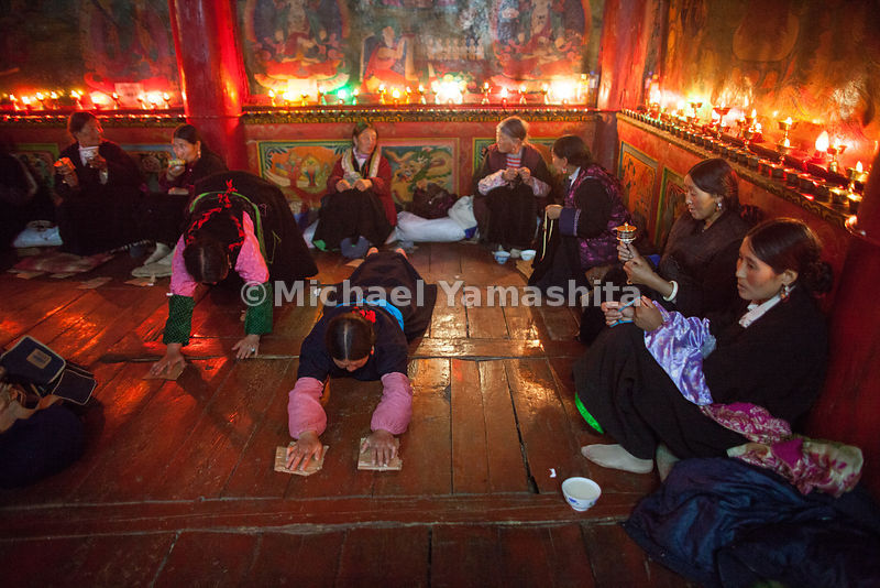 Local women share in the celebration at Garthar Monastery by performing Shak Tsal, turning prayer wheels and fingering prayer beads while muttering the mantra Om Mane Pad Me Um-All in the glow of yak butter lamps.