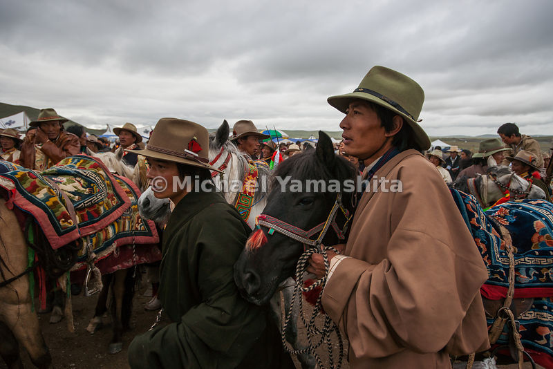 Tibetan cowboys in their long coats called chubas and stetson hats wait their turn to show off their horsemanship.