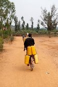 Cyclist carrying heavy water containers along street. Rwanda
