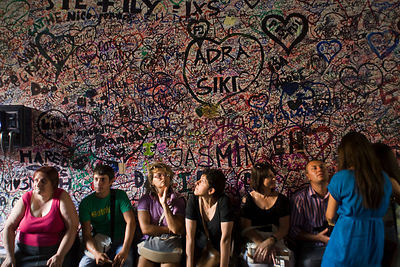 Italy - Verona - Tourists sit beneath graffiti on a wall at the entrance to the Casa di Giulietta