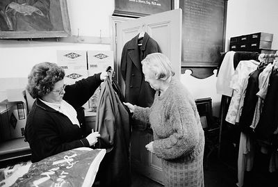 UK - London - A volunteer shows an elderly lady a donated coat at the Food for the Jewish Poor soup kitchen