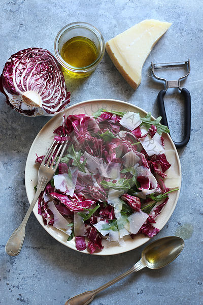 Radicchio salad with arugula and parmesan on a plate.Top view