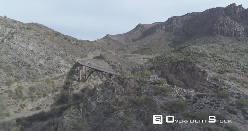 Wide tracking shot of cyclist going over bridge in dramatic scenery. Superior, Arizona, USA.