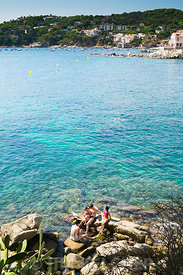 A young family enjoys a visit to the calm waters of the Costa Brava near the town of Calella de Palafrugell, Spain