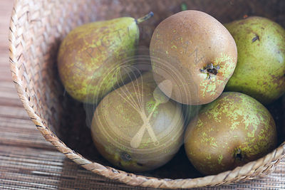 conference pears in woven basket, on woven mat, close up.
