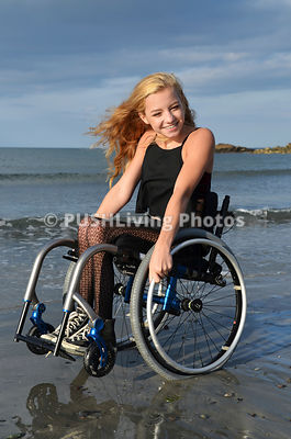 Young woman in a wheelchair on a beach