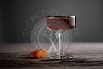 Sophisticated cocktail in a vintage, silver lined, coupe glass with orange peel on a rustic, gray wood surface.