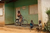 Local nurse outside her surgery with a Bicycle. Rwanda.