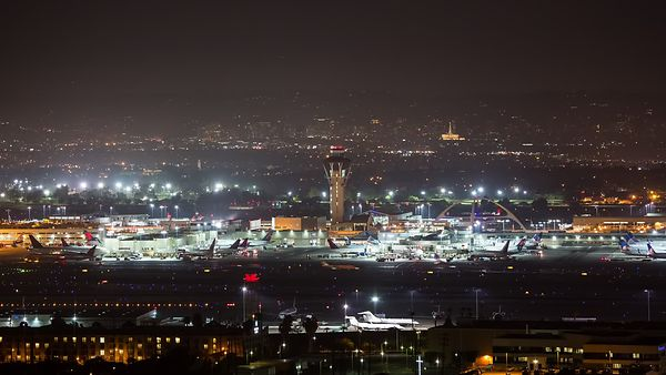Medium Bird's Eye Shot of Old & New Flight Control With Airplanes Lit at Night