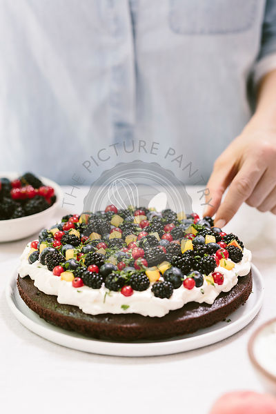 A woman is photographed from the front view as she was decorating the top of a chocolate cake with berries.