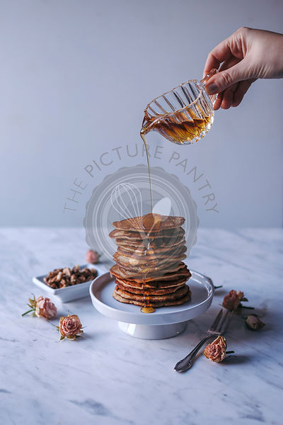 Woman puring maple syrup over stack of pancakes