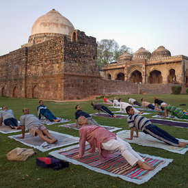 A yoga class in Lodi Gardens in front of the Bara Gumbad Tomb
