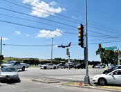 Airplane landing above car traffic at Love Field in Dallas, Texas
