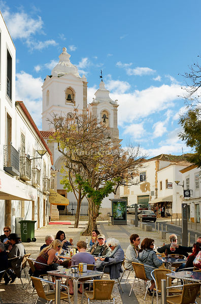 Tourists at a café and the church of Santo António. Lagos Portugal