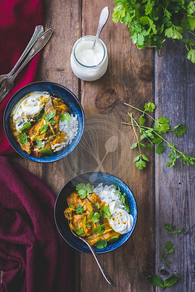 Aubergine curry with coriander and rice in bowls