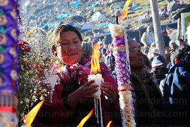 Pilgrim with burning candles at the last cross on the pilgrimage trail, Qoyllur Riti festival, Peru