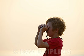 Young boy bird watching at Snettisham RSPB Reserve on the Wash Norfolk on a summer evening