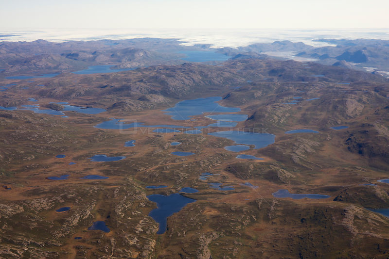 Aerial view of the landscape of the south-west coast of Greenland between Kangerlussuaq and Ilulissat, with glaciers stretching out of the ice shield towards the sea.