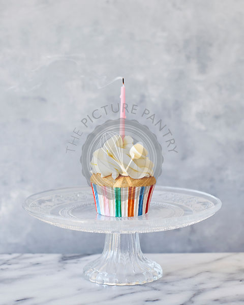 Party cupcake with pink candle on cake stand