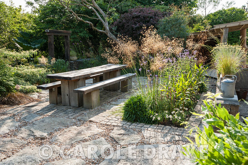 Chunky oak table and benches on a sunny terrace beside the house, with Stipa gigantea, Verbena bonariensis and salvias in adjoining bed and archway made of railway sleepers beyond, marking steps that lead down into the woodland garden. The 'Garten' Garden, Lower Treculliacks Farm, Falmouth, Cornwall, UK