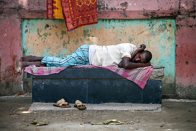 A worker rests on a bench on Strand Road, Kolkata, India. Strand Road is an extremely busy distribution hub in Kolkata.