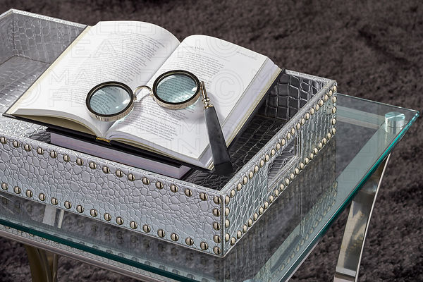 eyeglasses resting on open book in silver studded tray on glass top side table