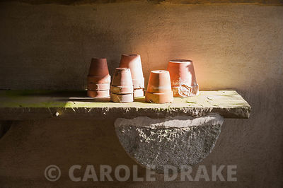 Terracotta pots on stone bench in the potting shed. York Gate Garden, Adel, Leeds, Yorkshire