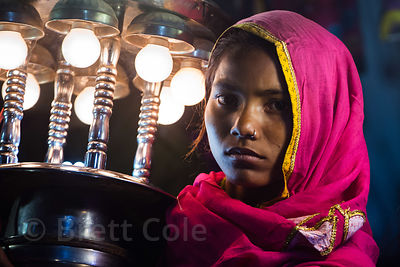 A woman carries a lantern during a marriage procession, Badi Basti, Pushkar, Rajasthan, India. Low caste adults are paid just 10 cents per hour to do this work.