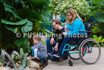 Young mother in a wheelchair with her family at a botanical garden