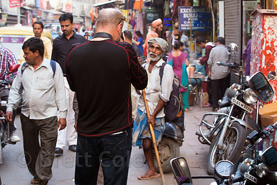 Tourist photographs a man pandhandling who is missing one leg, Paharganj, Delhi, India