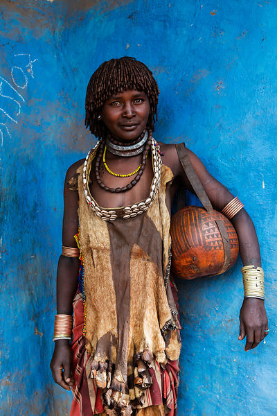 Hamar Woman Holding a Gourd Basket against a Blue Wall