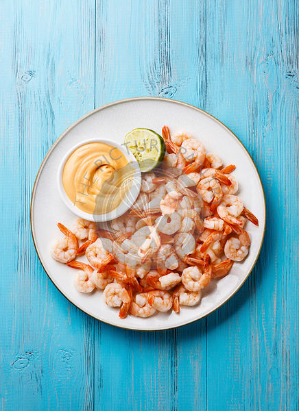 Prawns shrimps with cocktail sauce on white plate on blue background