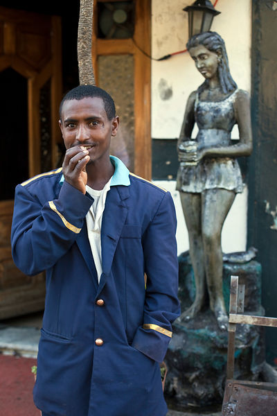 Ethiopia - Addis Ababa - A waiter outside a bar cleans his teeth with a twig, Addis Ababa, Ethiopia.